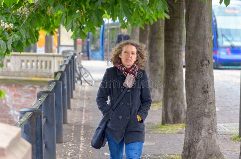 Donna che cammina espressamente attraverso la città immagine stock