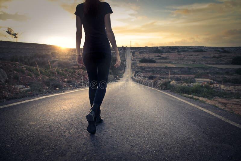 Donna che cammina giù una via fotografie stock libere da diritti