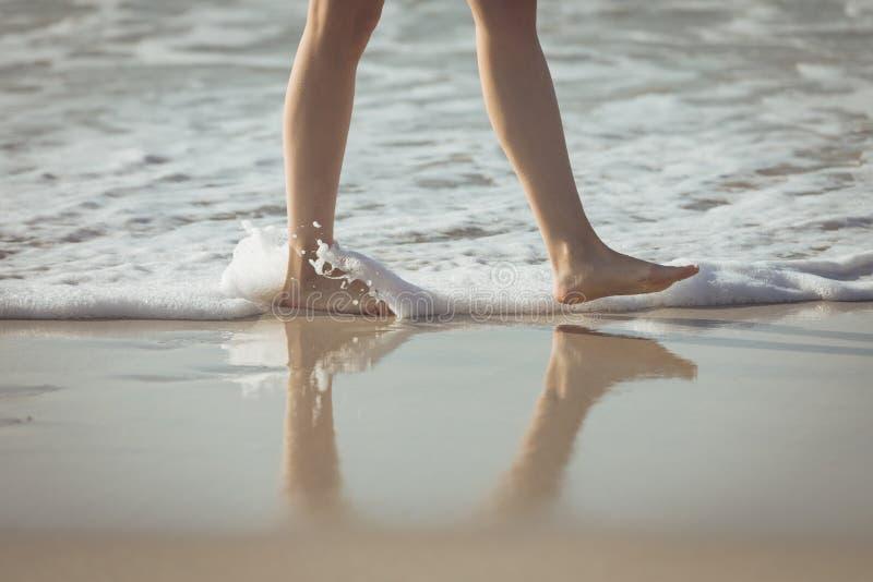 Donna che cammina lungo l'oceano alla spiaggia fotografia stock libera da diritti