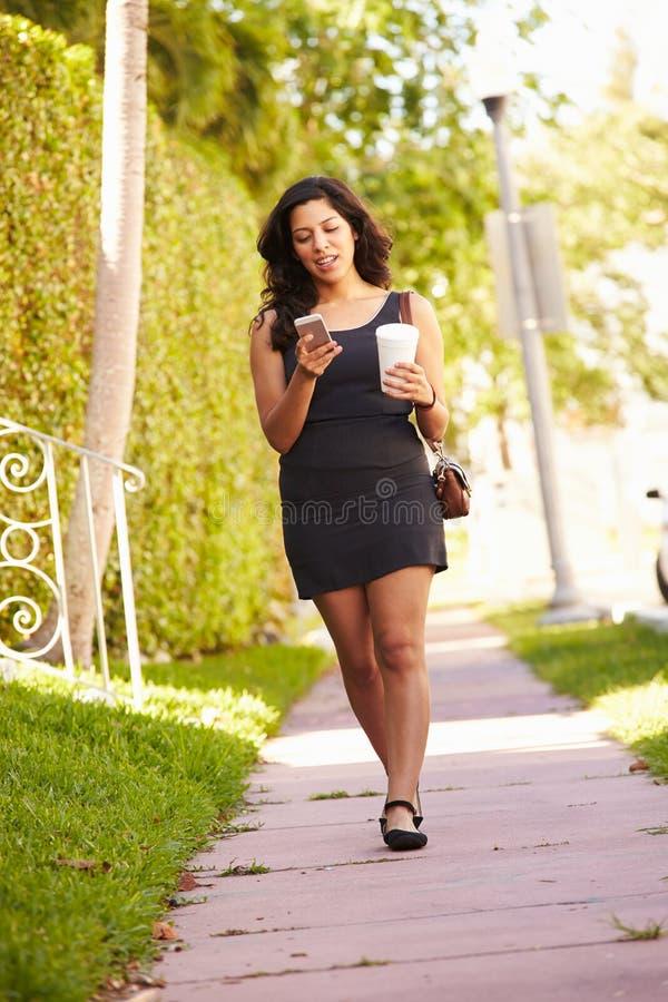 Donna che cammina lungo la via per lavorare facendo uso del telefono cellulare fotografia stock libera da diritti