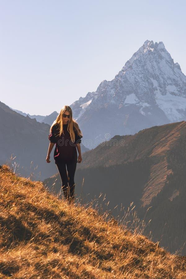 Donna che cammina nell'avventura sola di viaggio delle montagne fotografie stock