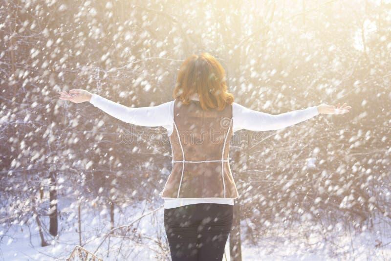 Donna che cammina nell'inverno nella foresta immagini stock libere da diritti