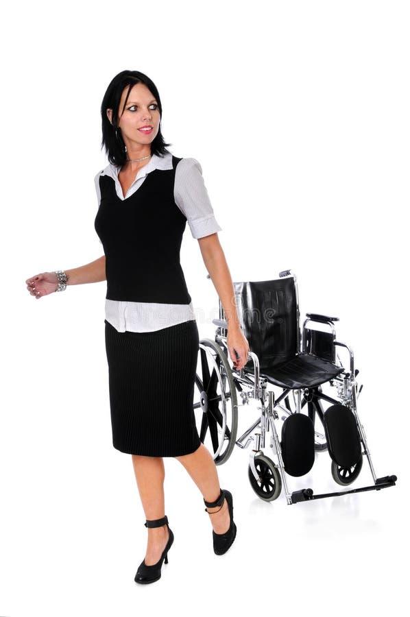 Donna che cammina a partire dalla sedia a rotelle fotografia stock