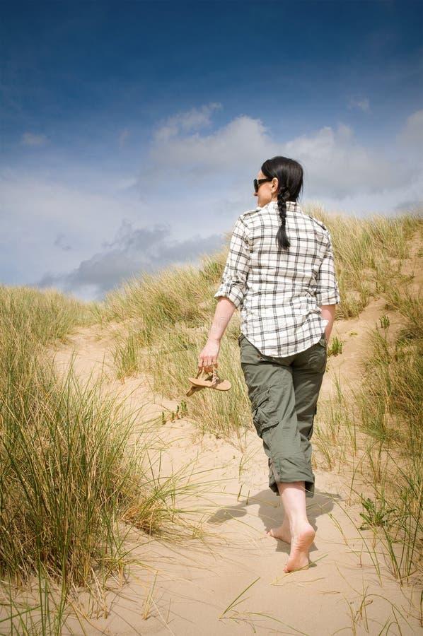 Donna che cammina per tirare in dune di sabbia fotografia stock libera da diritti