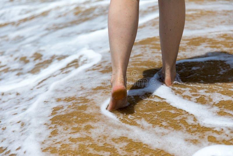 Donna che cammina a piedi nudi su una spiaggia Chiuda sulla gamba della giovane donna che cammina lungo l'onda dell'acqua e della fotografia stock