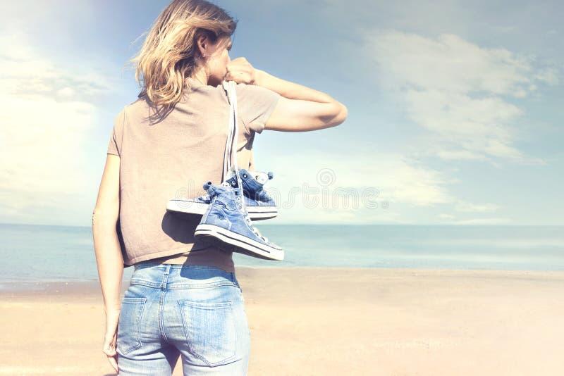 Donna che cammina a piedi nudi sulla spiaggia nella libertà fotografie stock