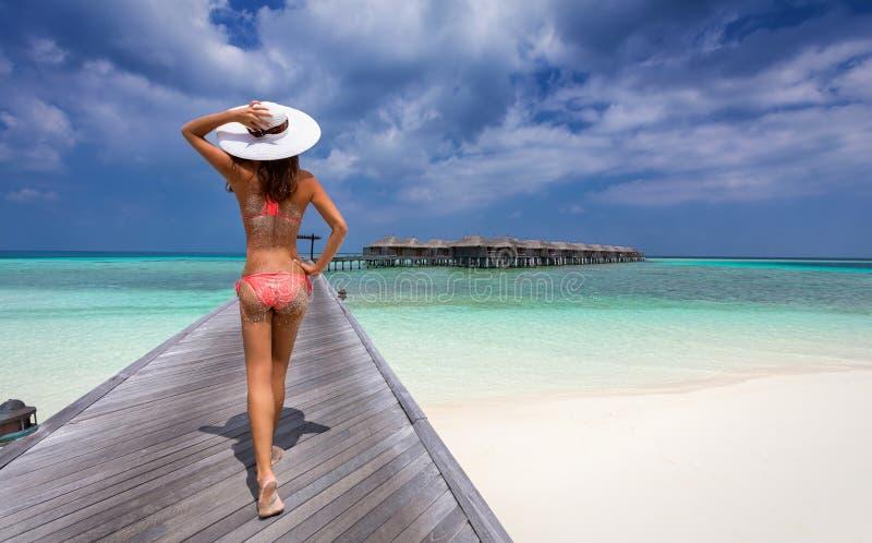 Donna che cammina sopra un molo in Maldive fotografie stock libere da diritti