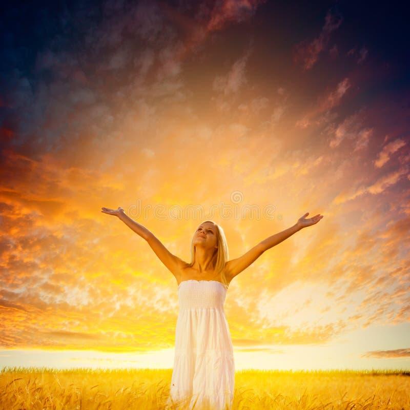 Donna che cammina sul giacimento di grano sopra il tramonto immagine stock libera da diritti