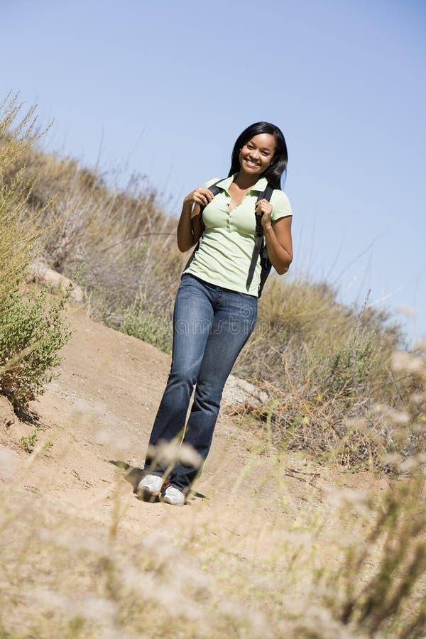 Donna che cammina sul sorridere del percorso della spiaggia fotografia stock libera da diritti