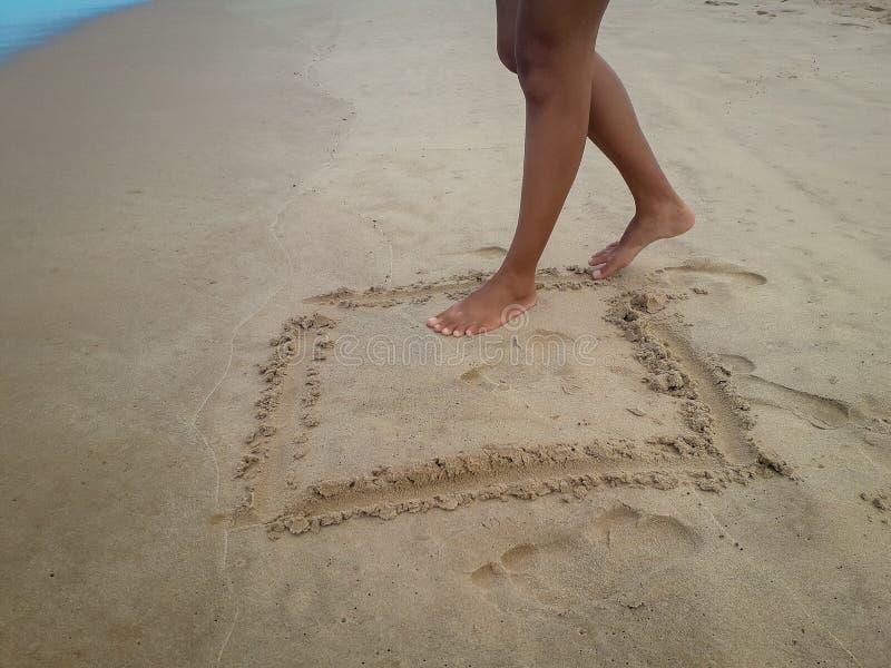 Donna che cammina sulla spiaggia di sabbia che lascia le orme nella sabbia Dettaglio del primo piano dei piedi femminili al Brasi fotografia stock libera da diritti