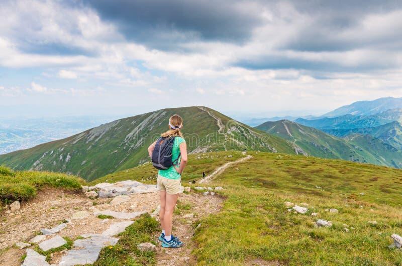 Donna che cammina sulla traccia di montagna immagine stock