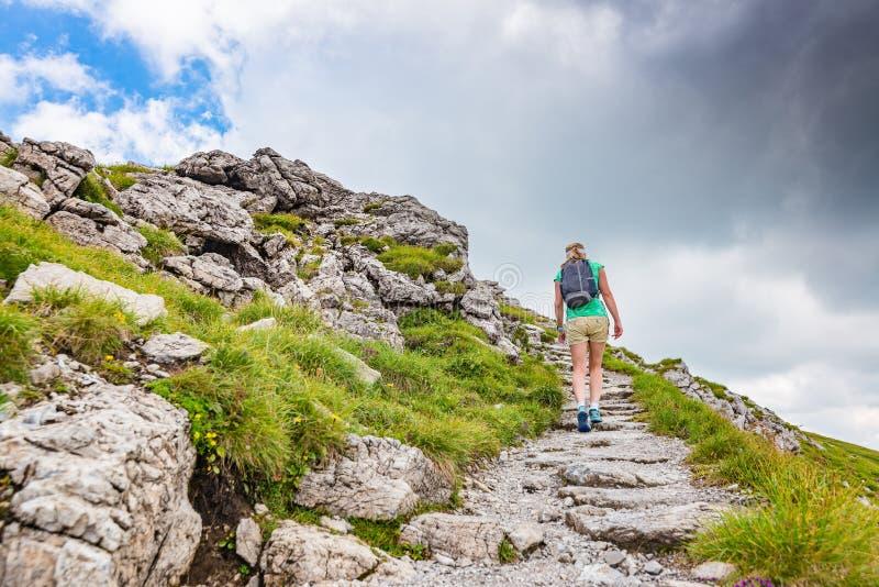 Donna che cammina sulla traccia di montagna fotografie stock libere da diritti