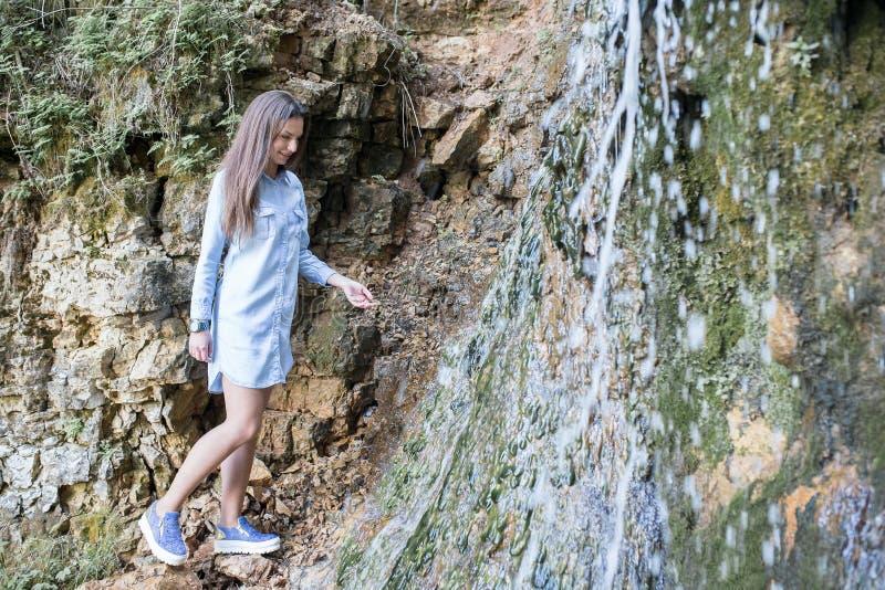 Donna che cammina vicino alle cascate della montagna immagini stock libere da diritti