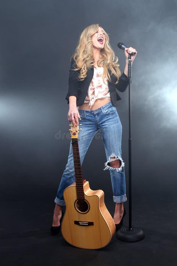 Donna che canta in scena con il Mic e la chitarra fotografia stock