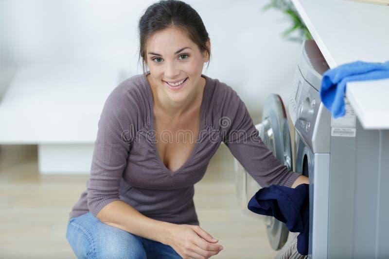 Donna che carica i vestiti sporchi in lavatrice fotografia stock libera da diritti