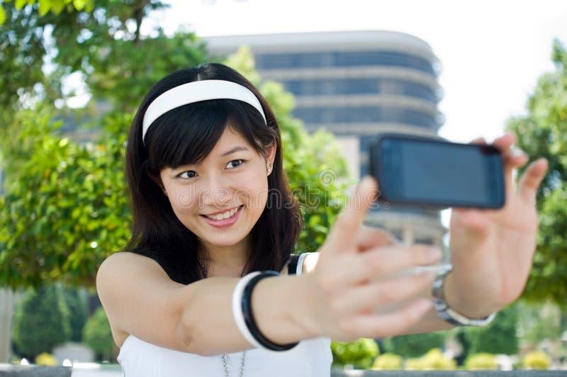 Donna che cattura auto ritratto fotografia stock