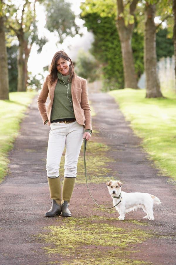 Donna che cattura cane per la camminata all'aperto nella sosta di autunno immagini stock libere da diritti