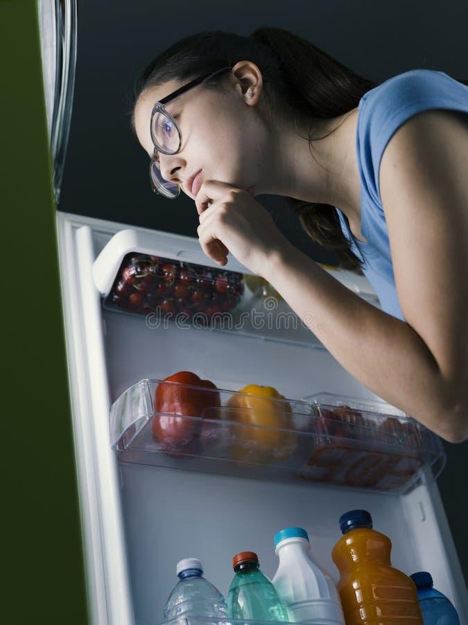 Donna che cerca l'alimento nel frigorifero fotografie stock libere da diritti