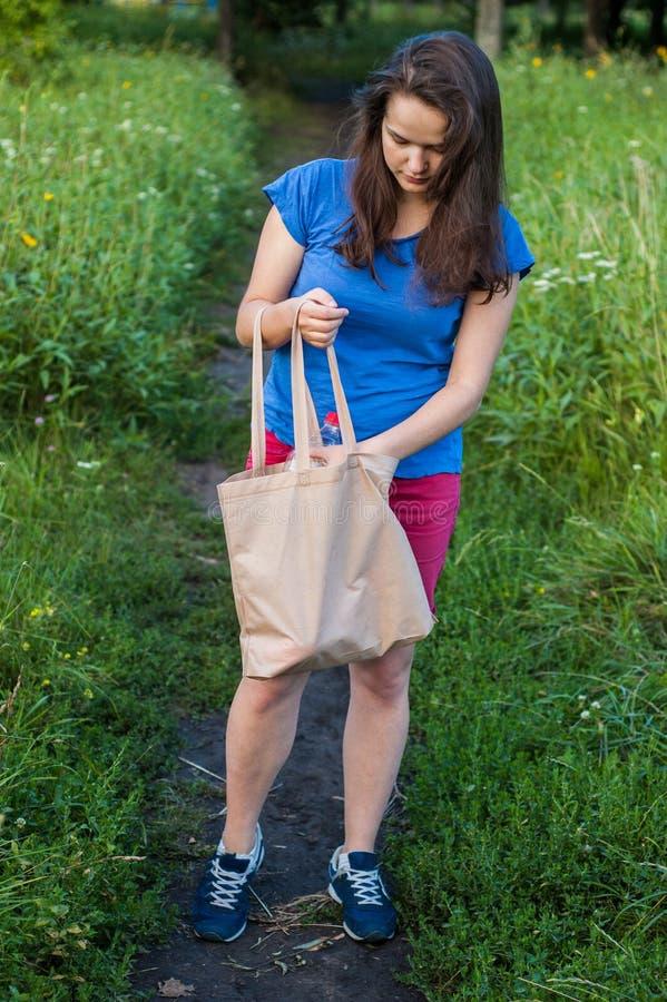 Donna che cerca qualcosa in una borsa immagine stock libera da diritti