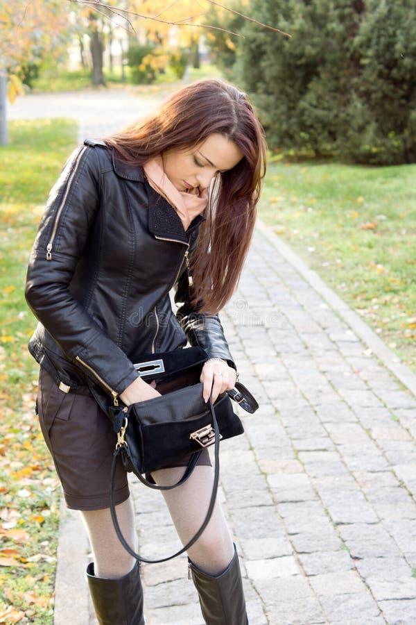 Donna che cerca in sua borsa fotografia stock