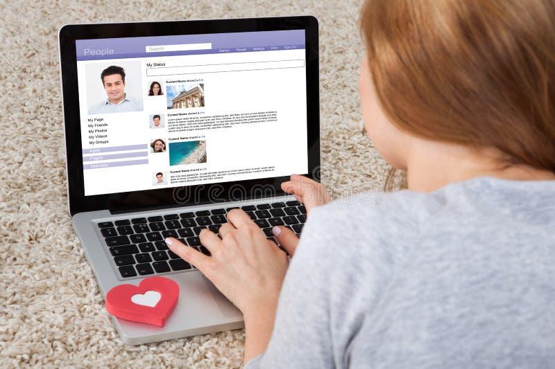 Donna che chiacchiera sul computer portatile immagine stock libera da diritti