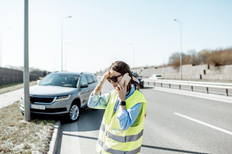 Donna che chiama durante l'incidente stradale sulla strada principale immagine stock libera da diritti