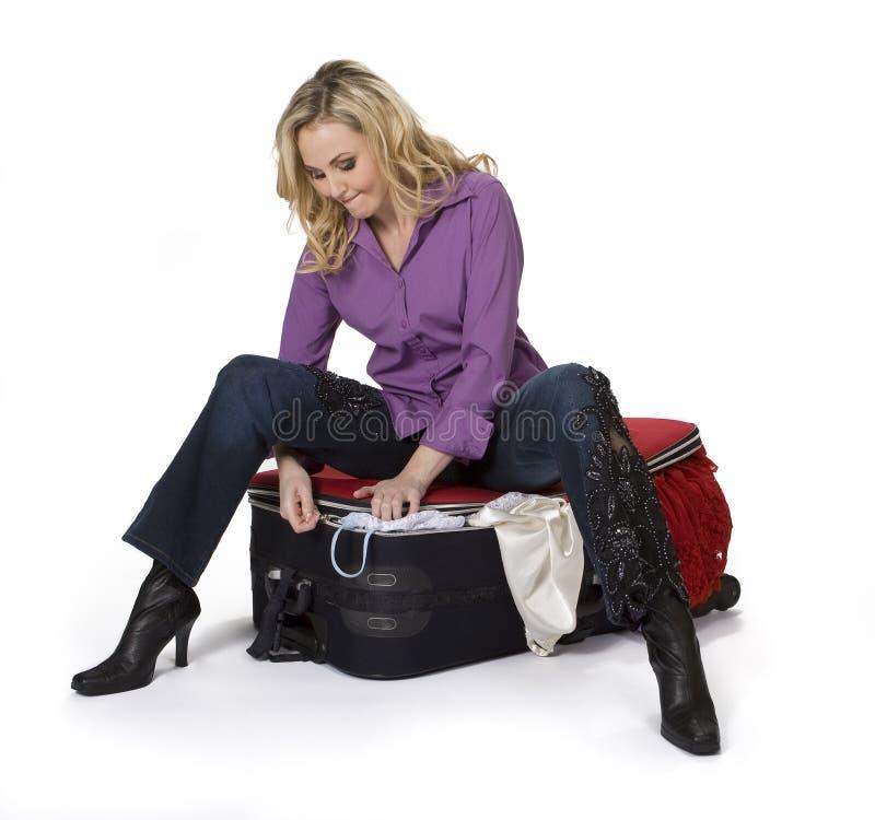 Donna che chiude la sua valigia immagine stock libera da diritti