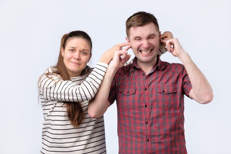 Donna che chiude le sue orecchie del marito vuole tenere qualcosa nel segreto immagini stock libere da diritti