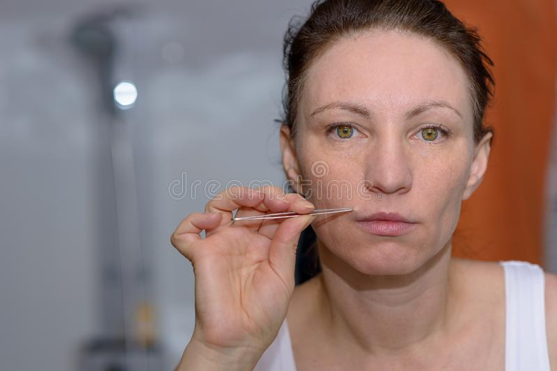 Donna che coglie i capelli lunghi sul suo labbro superiore immagini stock libere da diritti