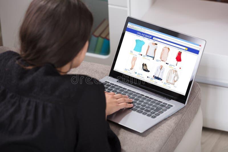 Donna che compera online facendo uso del computer portatile fotografia stock