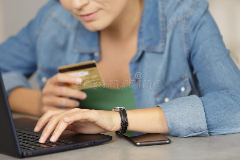 Donna che compra pagamento online sul numero di carta di credito della lettura del computer portatile fotografia stock libera da diritti