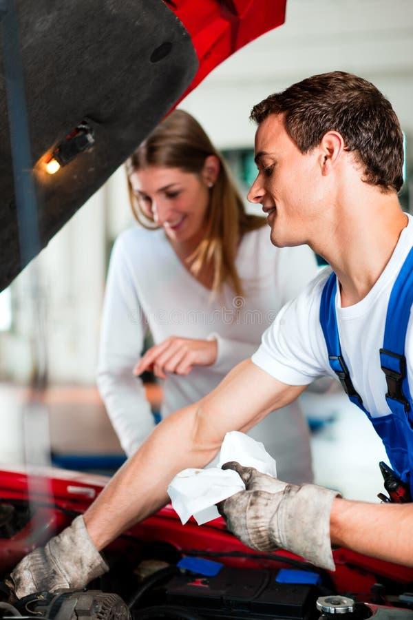 Donna che comunica con meccanico di automobile nell'officina riparazioni immagini stock