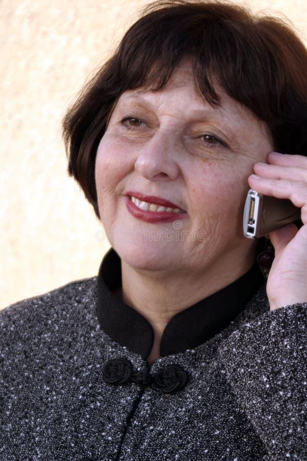 Donna che comunica sul telefono immagine stock