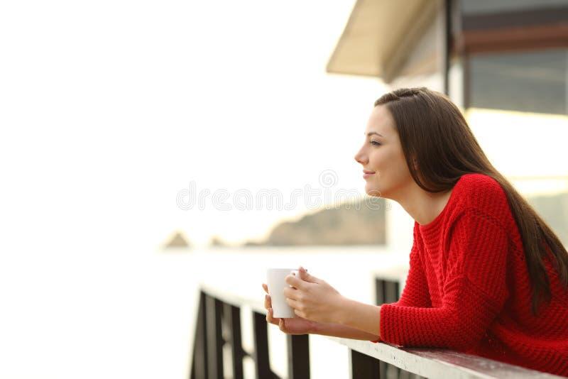 Donna che contempla le viste della spiaggia dall'hotel fotografia stock