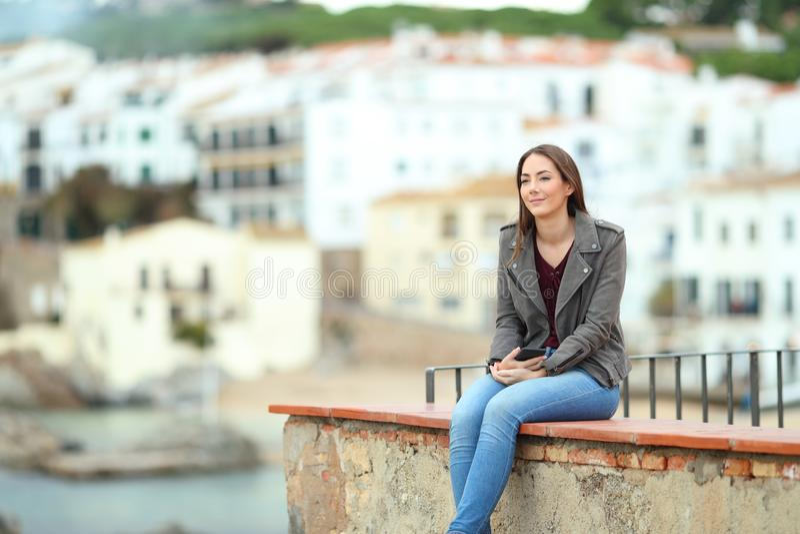 Donna che contempla oceano in una città della costa fotografie stock