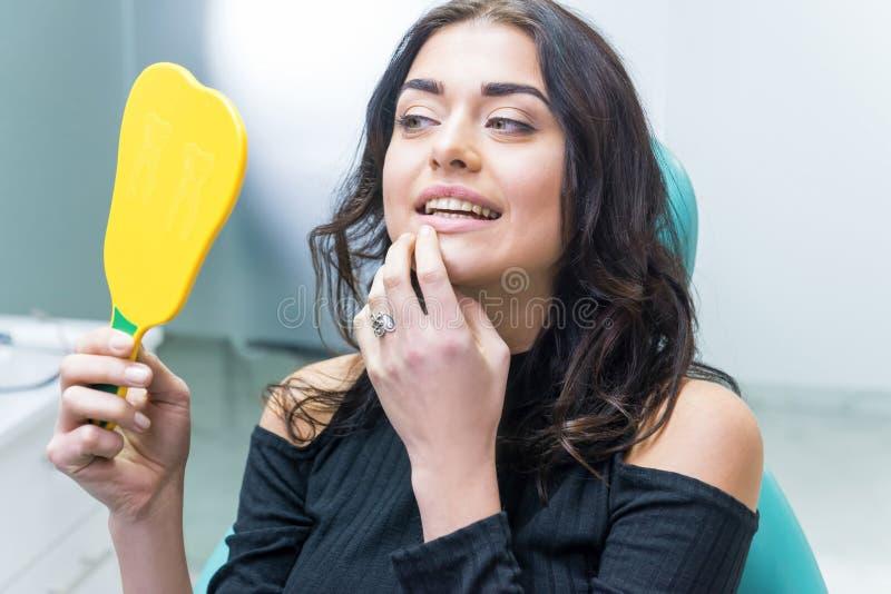 Donna che controlla i denti in specchio immagini stock libere da diritti