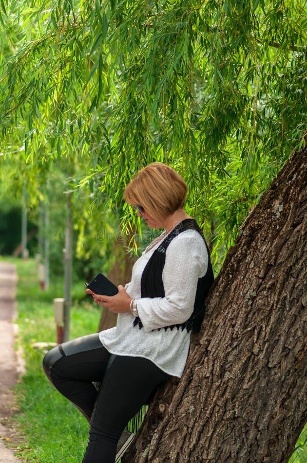 Donna che controlla il suo telefono immagini stock