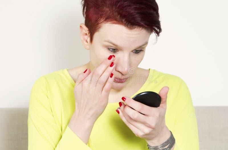 Donna che controlla il suo trucco in piccolo specchio fotografia stock