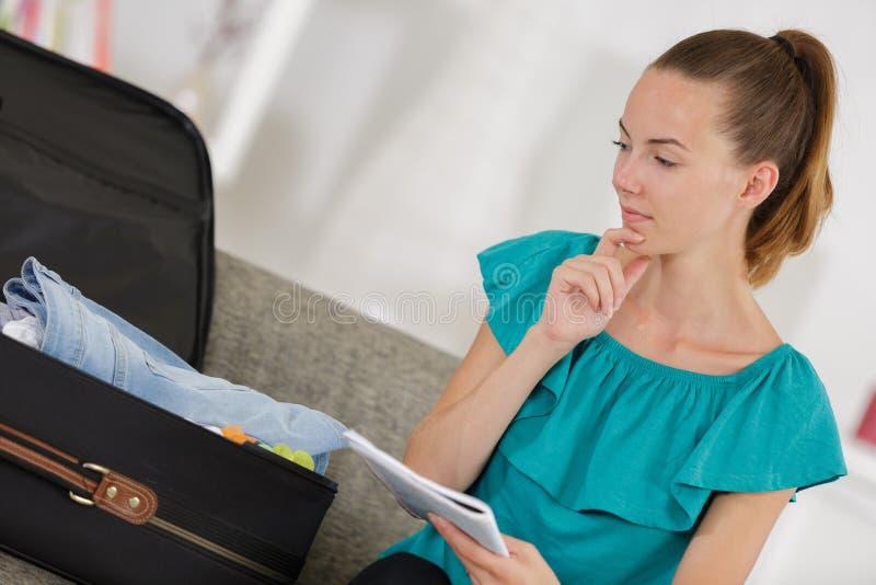 Donna che controlla la lista di imballaggio immagine stock libera da diritti