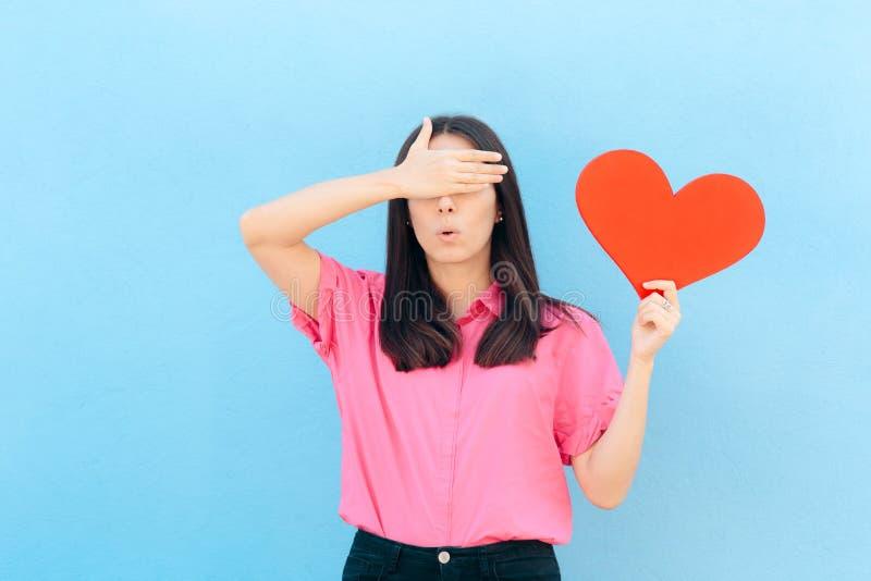 Donna che copre i suoi occhi che tengono grande cuore immagini stock libere da diritti