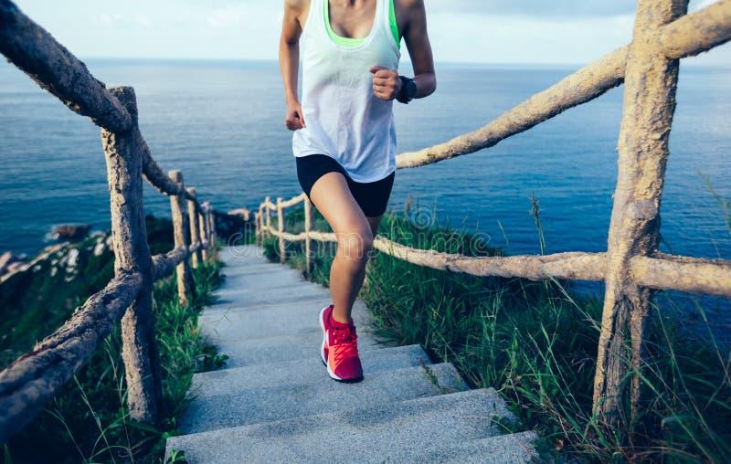 Donna che corre su sulla montagna della spiaggia fotografia stock libera da diritti