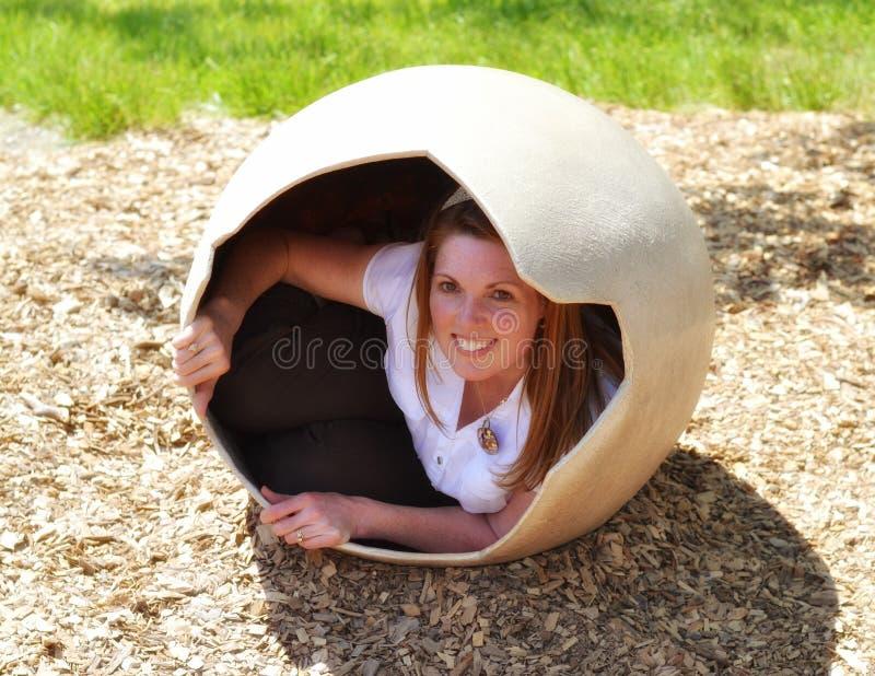 Donna che cova dal grande uovo fotografia stock