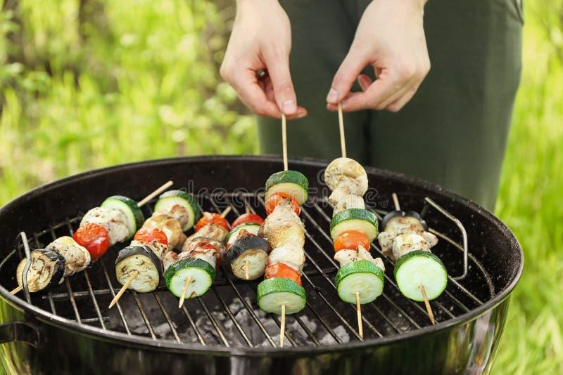 Donna che cucina carne succosa con le verdure sulla griglia del barbecue all'aperto immagini stock libere da diritti