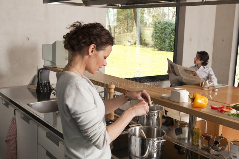 Donna che cucina il giornale della lettura dell'uomo immagine stock
