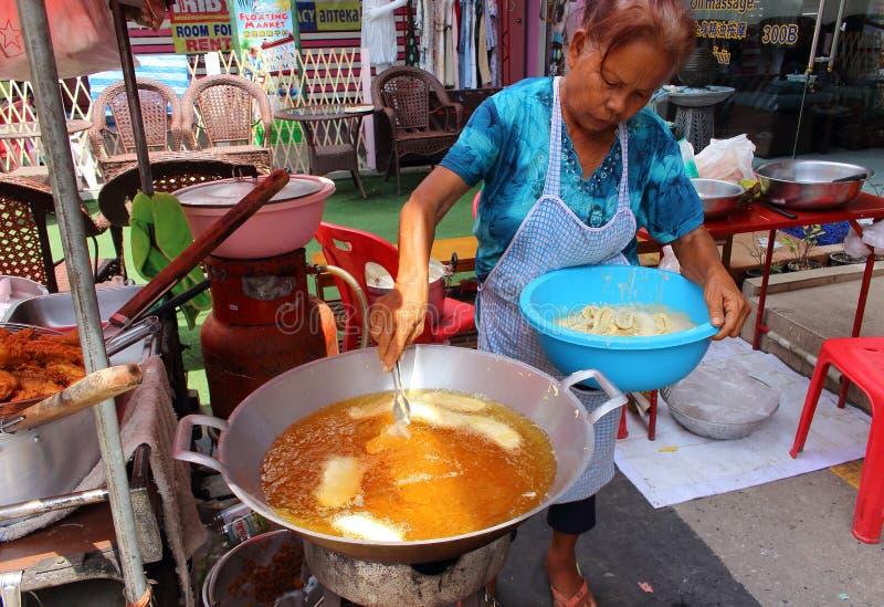 Donna che cucina le banane fritte in grasso bollente immagini stock