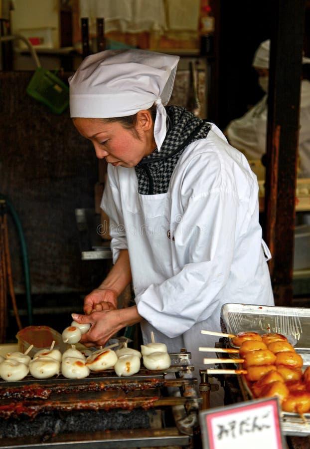 Donna che cucina Mitarashi dolce Dango immagine stock libera da diritti