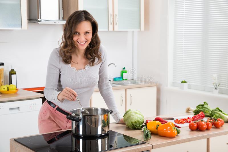 Donna che cucina pasto in cucina immagine stock
