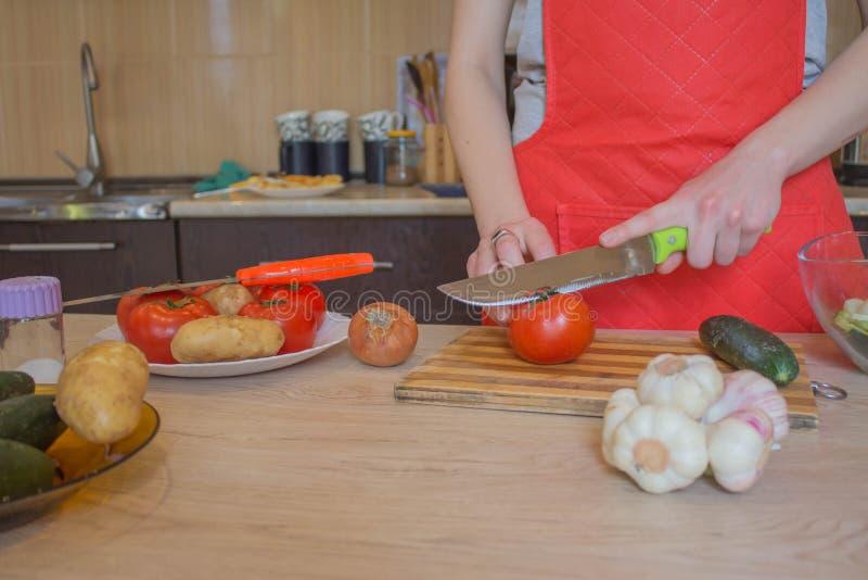 Donna che cucina pasto sano nella cucina Cucinando alimento sano a casa Donna in cucina che prepara le verdure Tagli del cuoco un fotografia stock libera da diritti