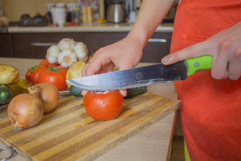 Donna che cucina pasto sano nella cucina Cucinando alimento sano a casa Donna in cucina che prepara le verdure Tagli del cuoco un fotografie stock