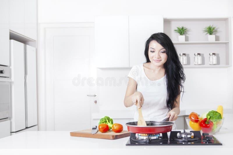 Donna che cucina sulla stufa con la frittura immagini stock libere da diritti